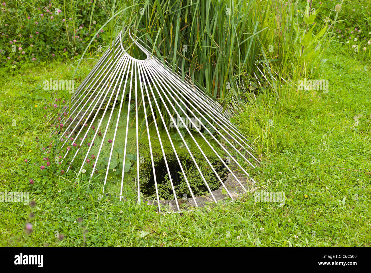 Unusual artistic protective grille around a small pool of water - Stock Image