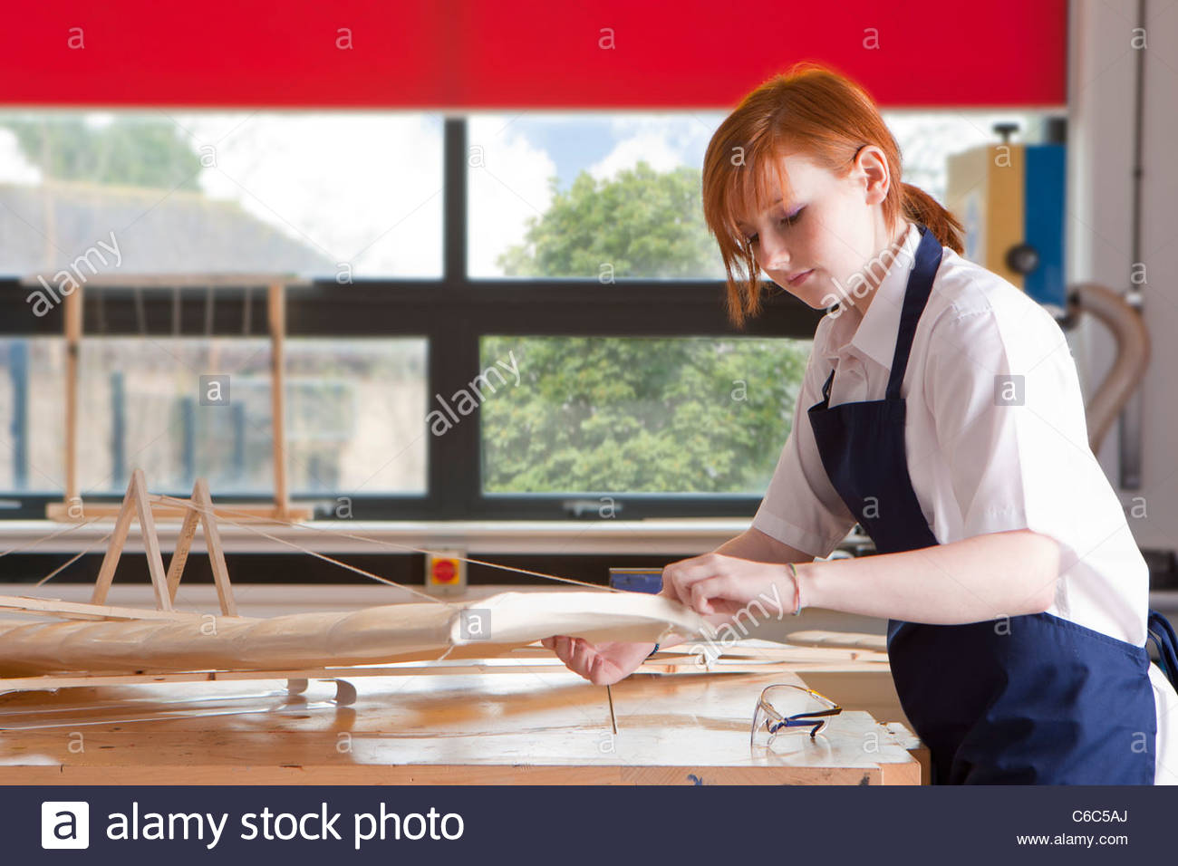 Student in woodworking class working on model airplane - Stock Image