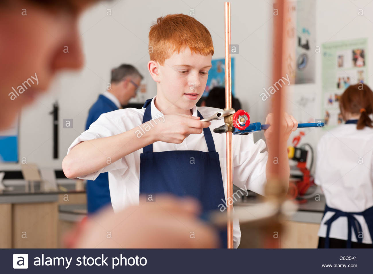 Student using wrench to tighten valve on cooper plumbing pipe - Stock Image