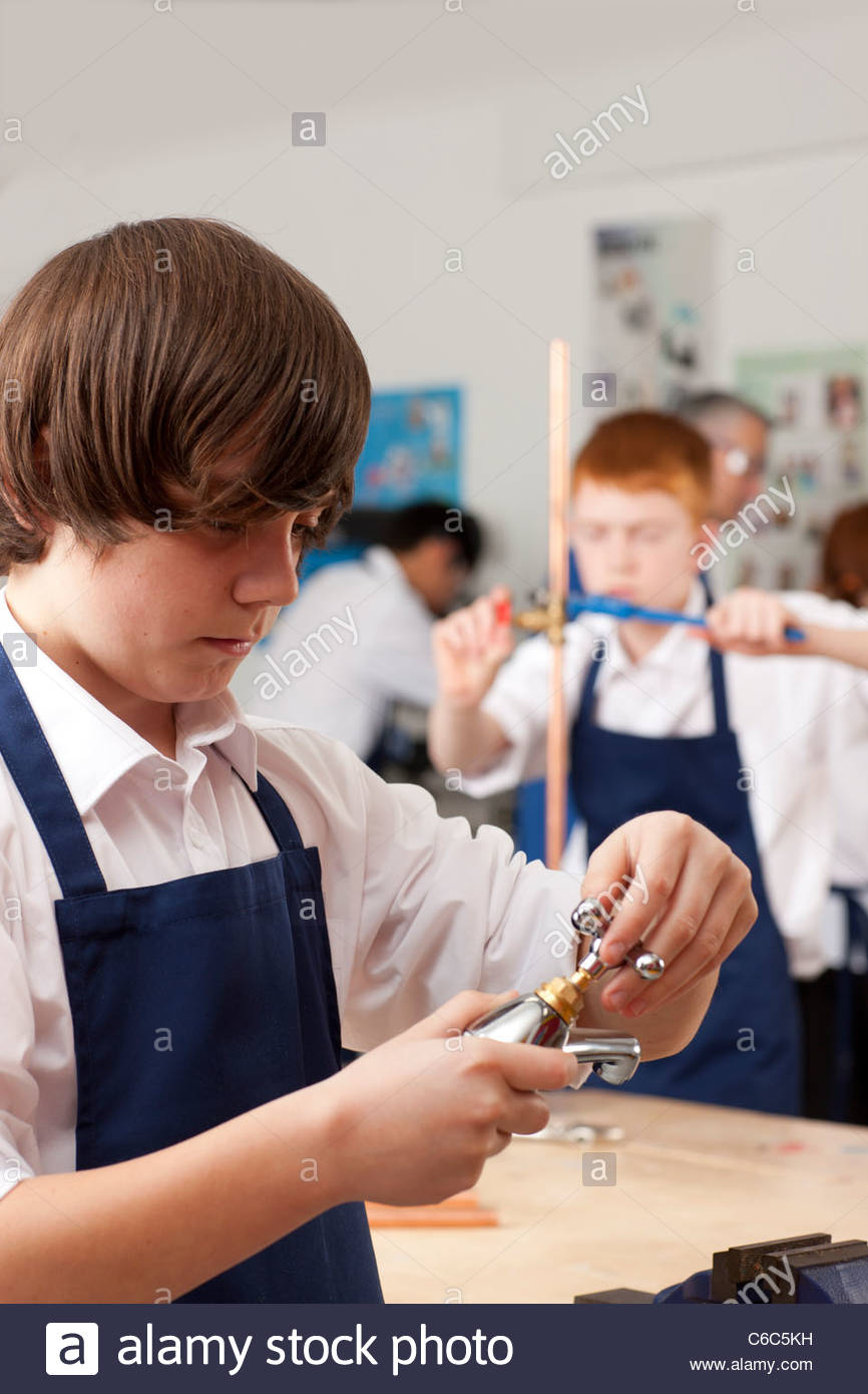 Student looking at plumbing faucet in vocational classroom - Stock Image