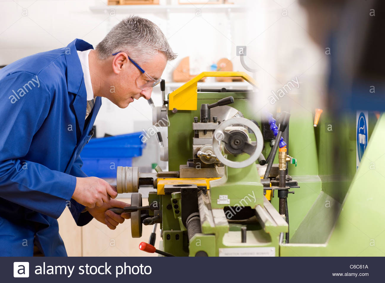 Metalworker using lathe in workshop - Stock Image