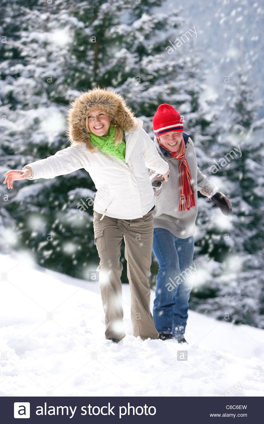 Couple walking in snowy woods - Stock Image