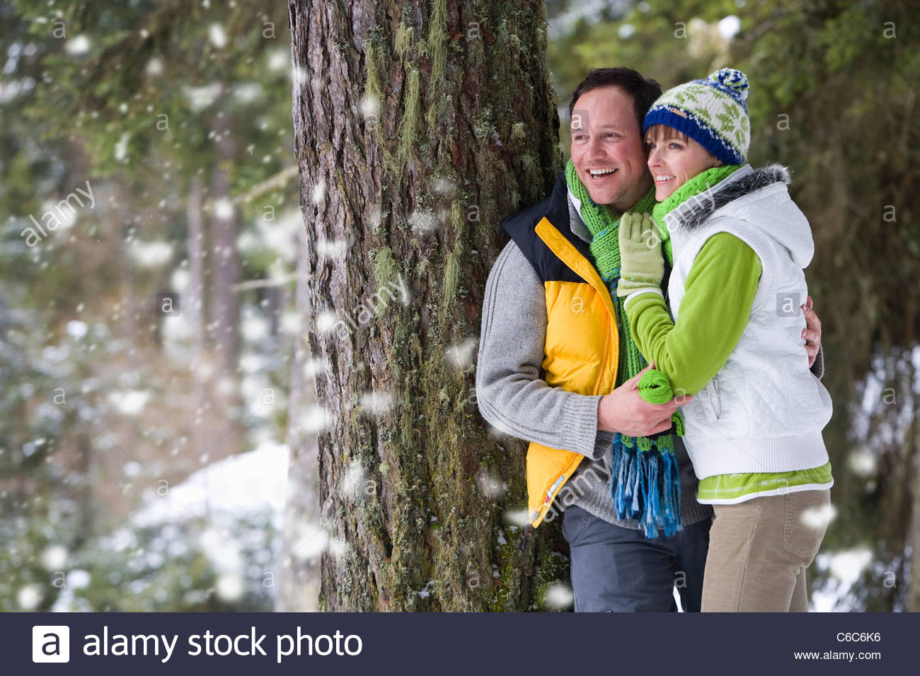 Couple leaning against tree and watching snow fall in woods - Stock Image