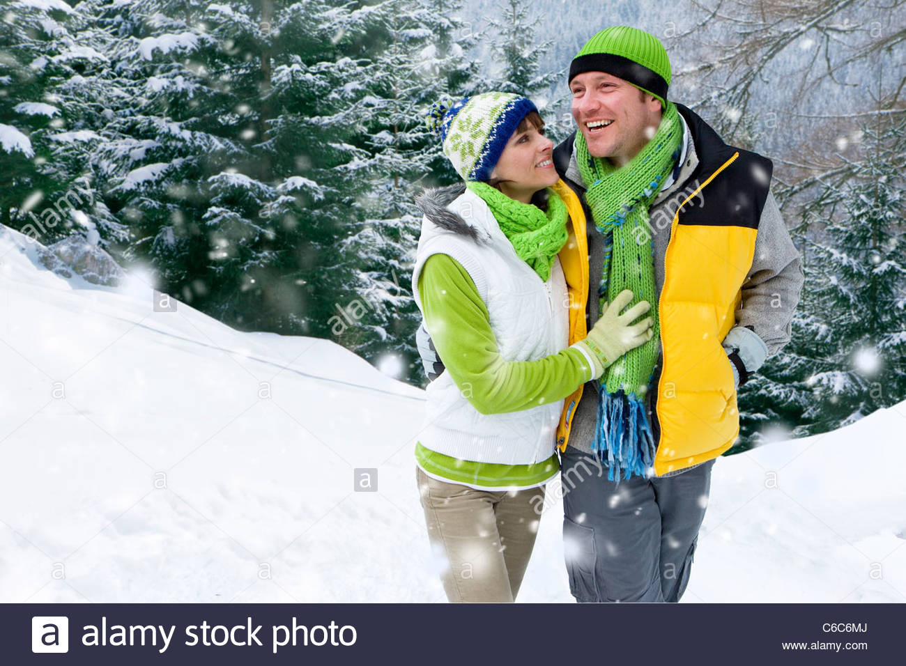 Smiling couple walking in snowy woods - Stock Image