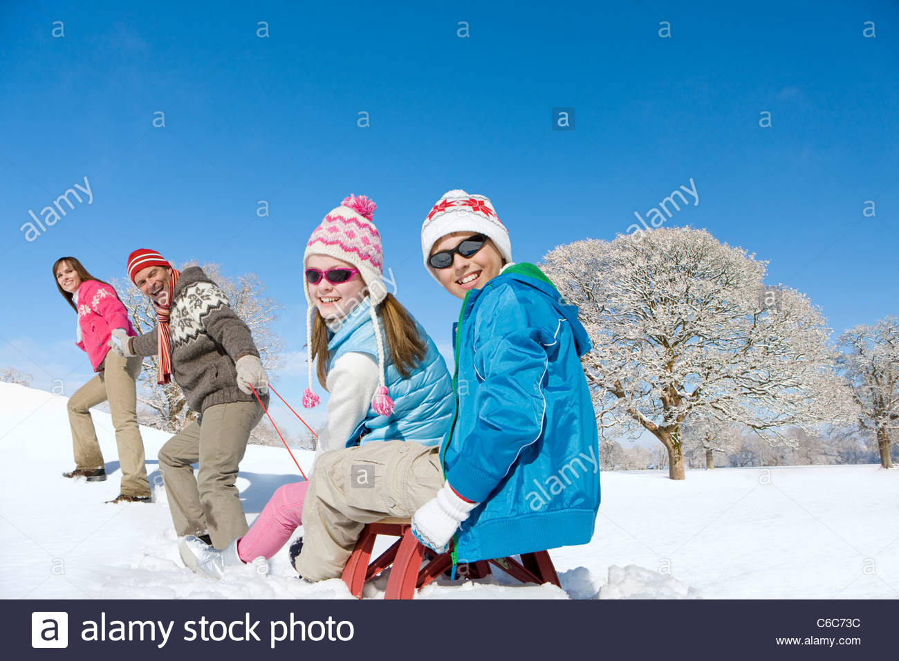 Portrait of parents pulling children on sled in sunny, snowy field - Stock Image