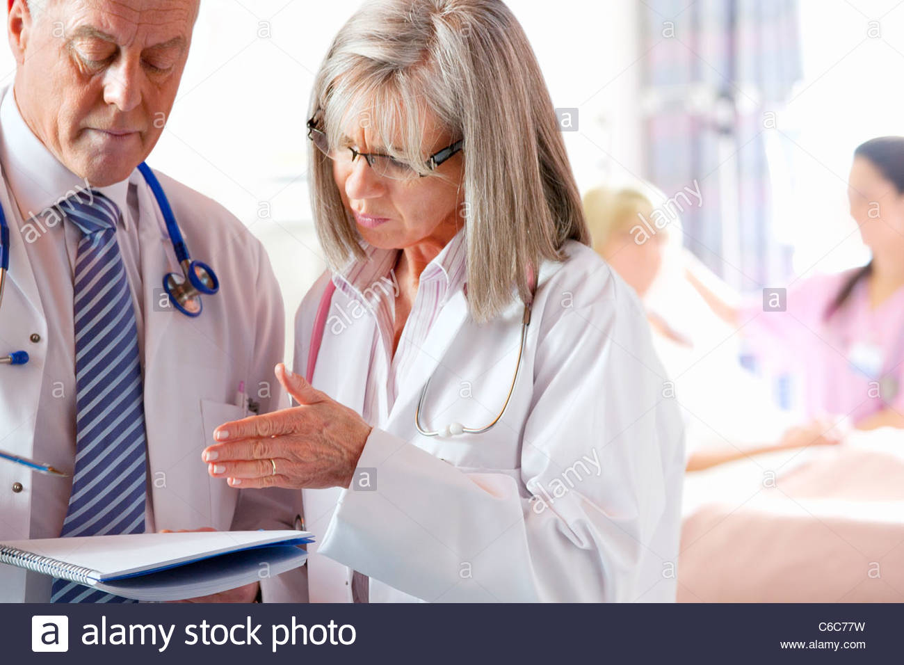 Doctors discussing medical chart in hospital with patient and nurse in background - Stock Image