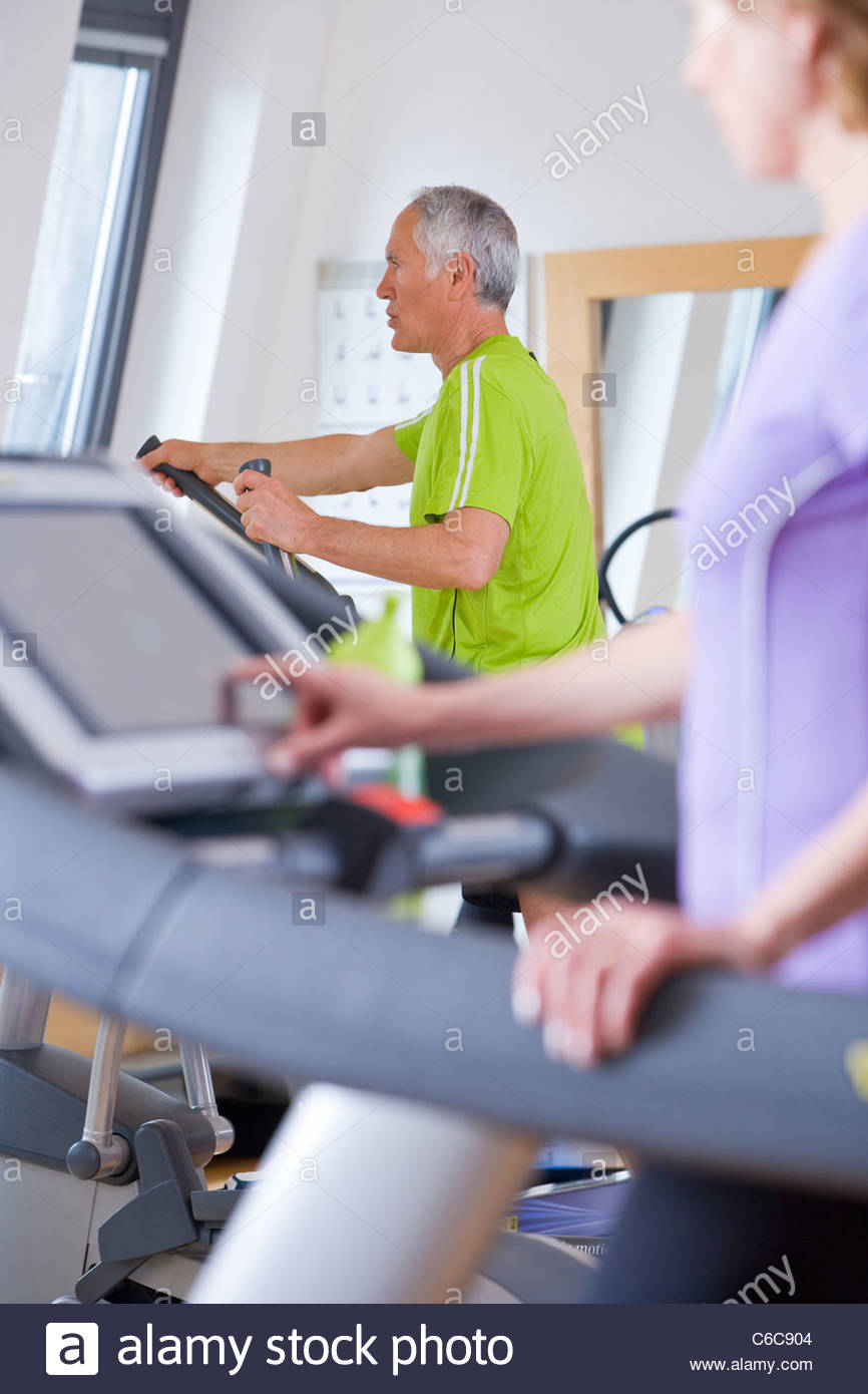 Senior man and woman exercising on treadmills in gym - Stock Image