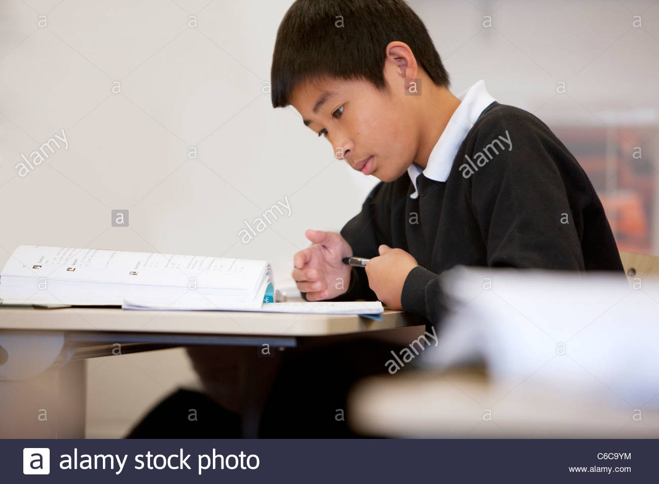 Focused boy doing homework at desk in classroom - Stock Image