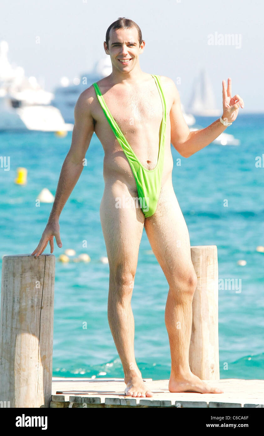 A Swiss tourist wears a funny bathing suit and amuses other tourists near Club 55 in Pampelona Beach. St. Tropez, Stock Photo