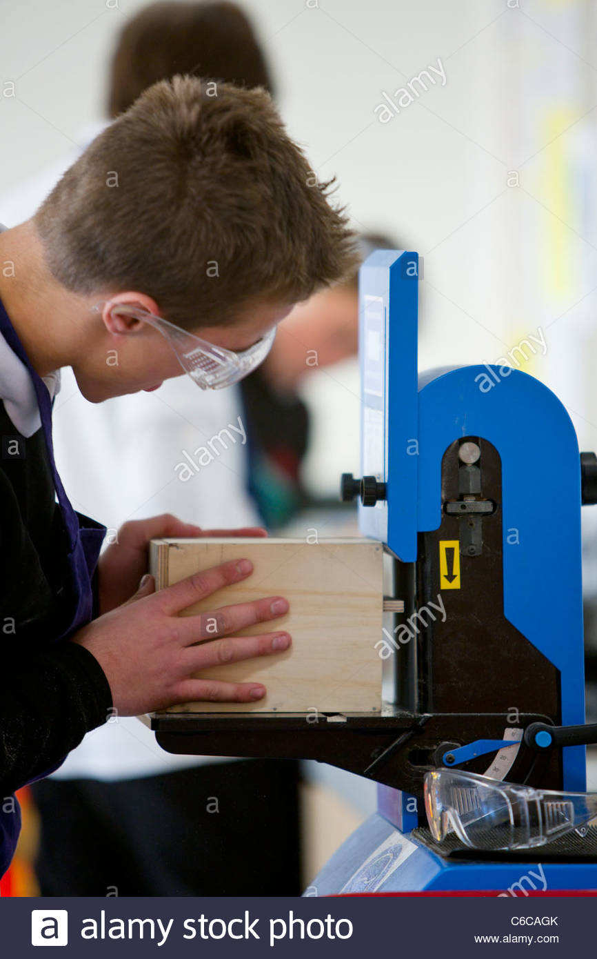 Boy with goggles using woodworking machinery in classroom workshop - Stock Image
