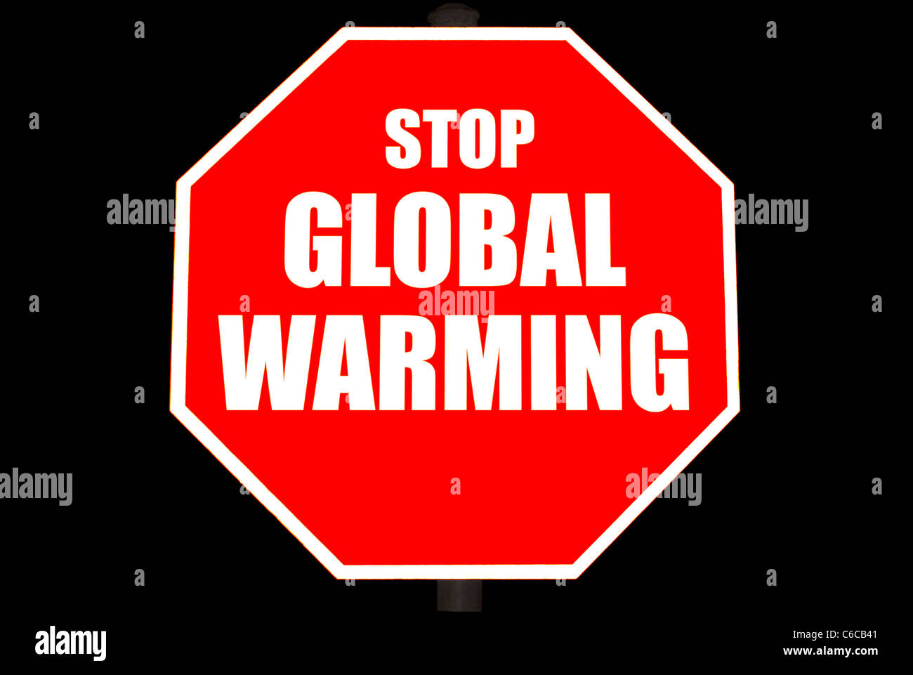 Bright red stop sign with STOP GLOBAL WARMING on it isolated on black - Stock Image
