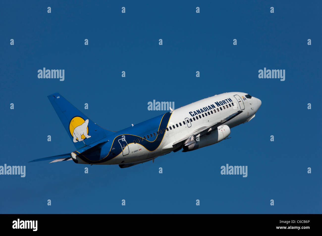 A Canadian North passenger jet aircraft sporting it's polar bear emblem takes off from Yellow Knife airport - Stock Image