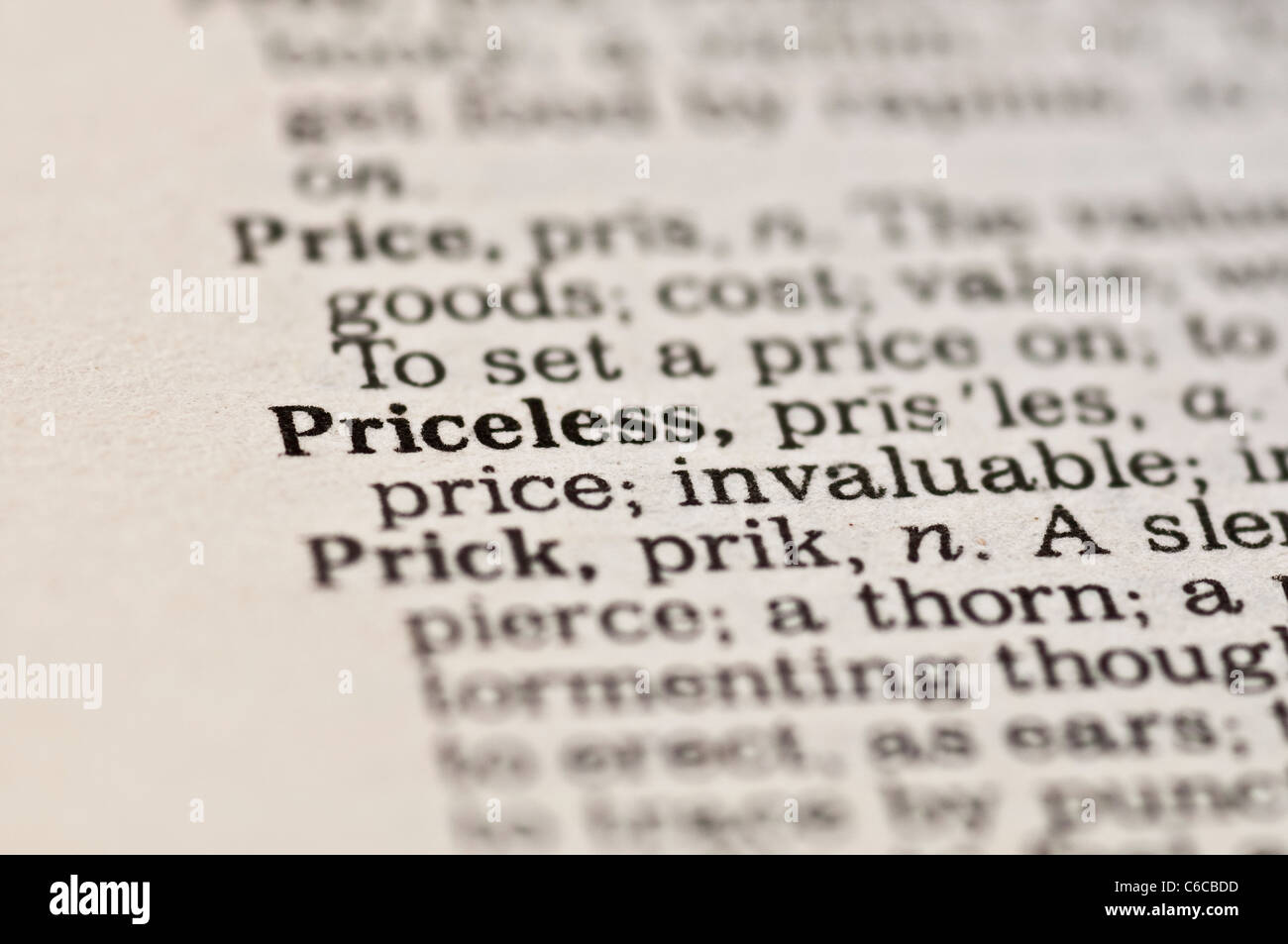 Extreme close up of the word PRICELESS found inside a dictionary - Stock Image