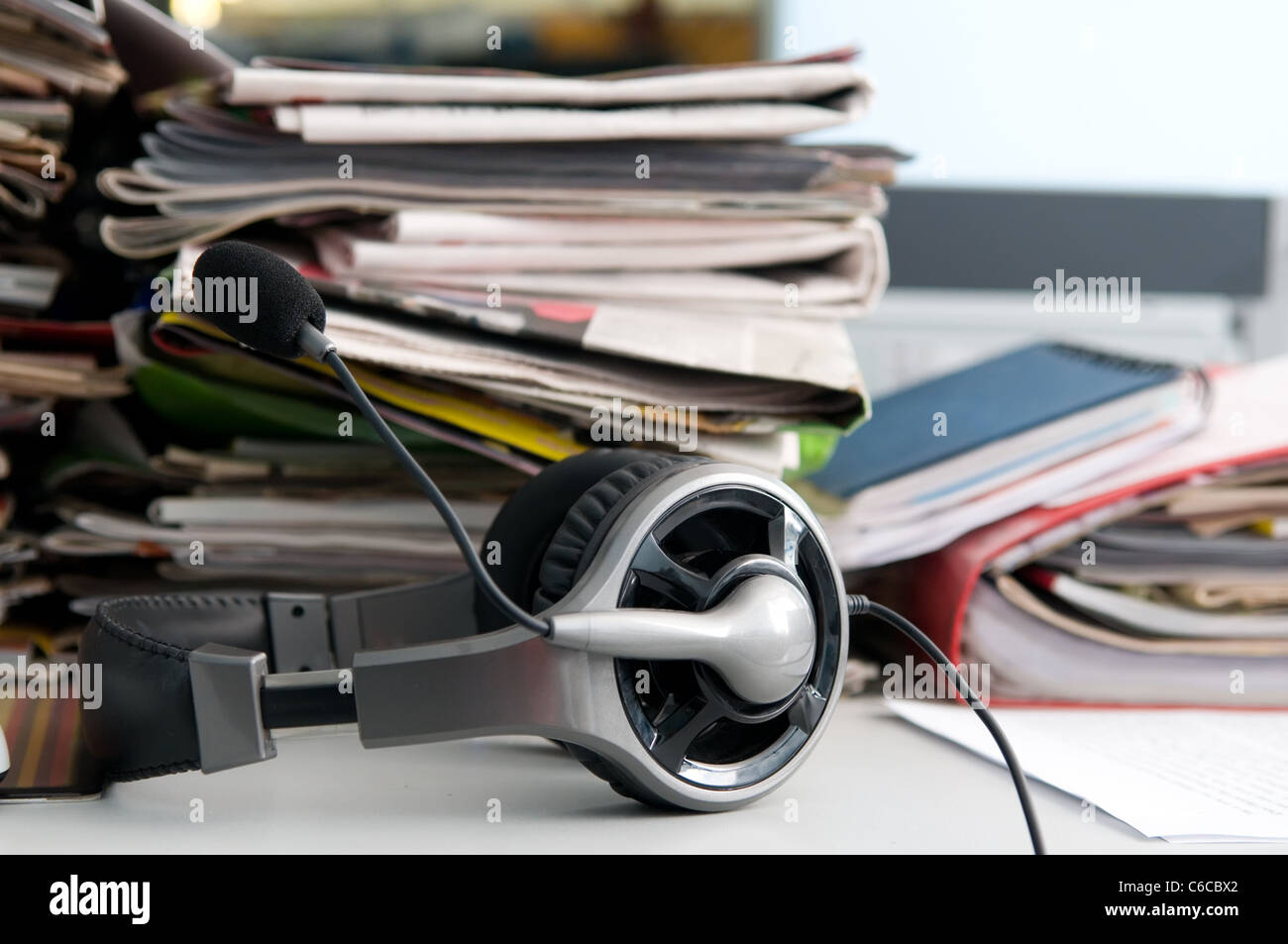 Headphones with a microphone and a mess on the table - Stock Image
