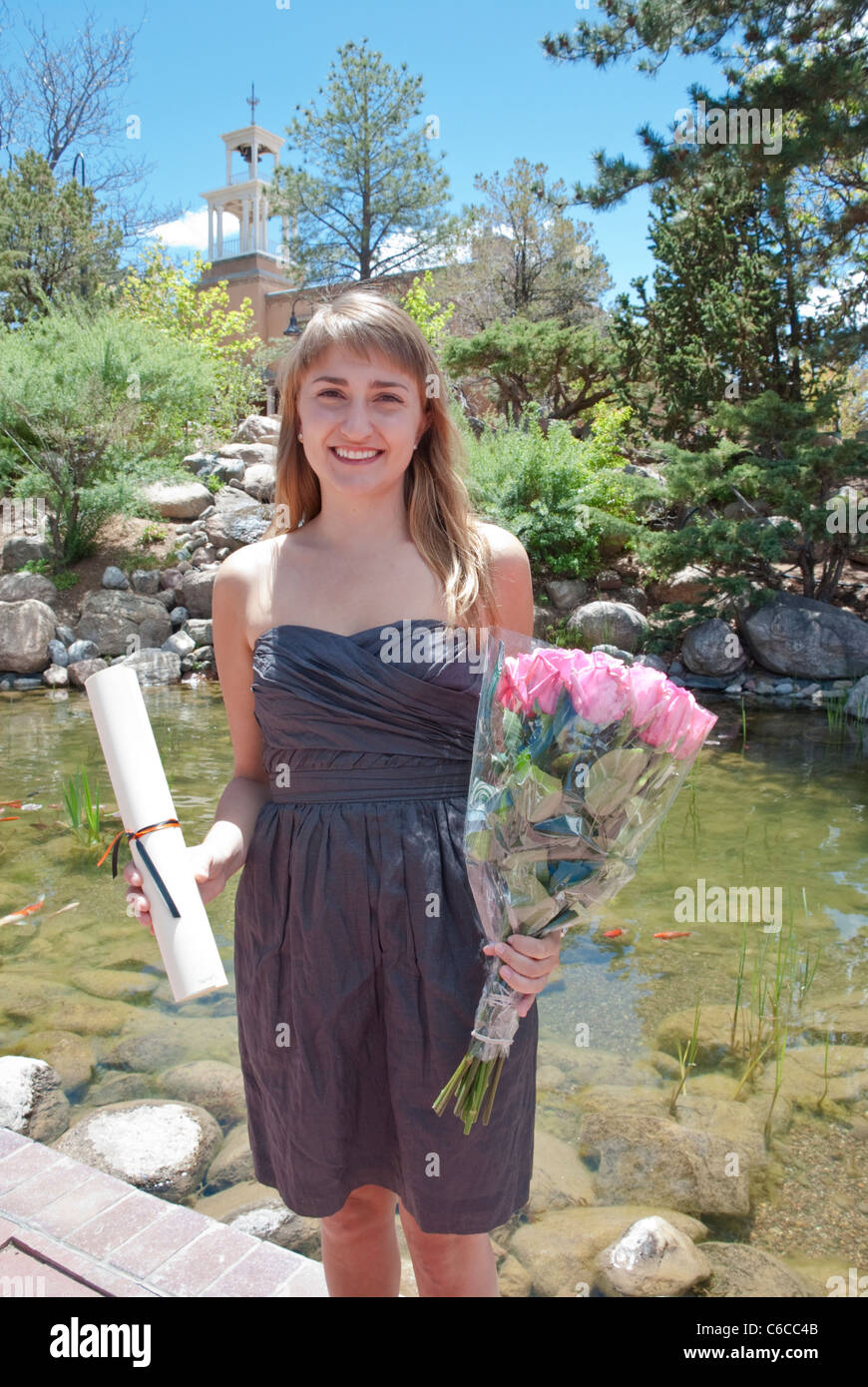 A graduating senior at St. Johns College in Santa Fe poses with her diploma and a bouquet of roses. - Stock Image