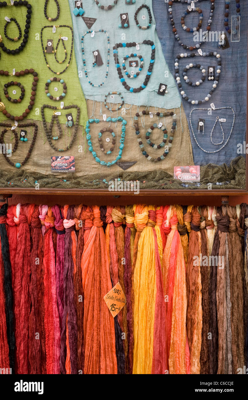 Multi coloured scarves, necklaces, earrings and bracelets in a shop display - Stock Image