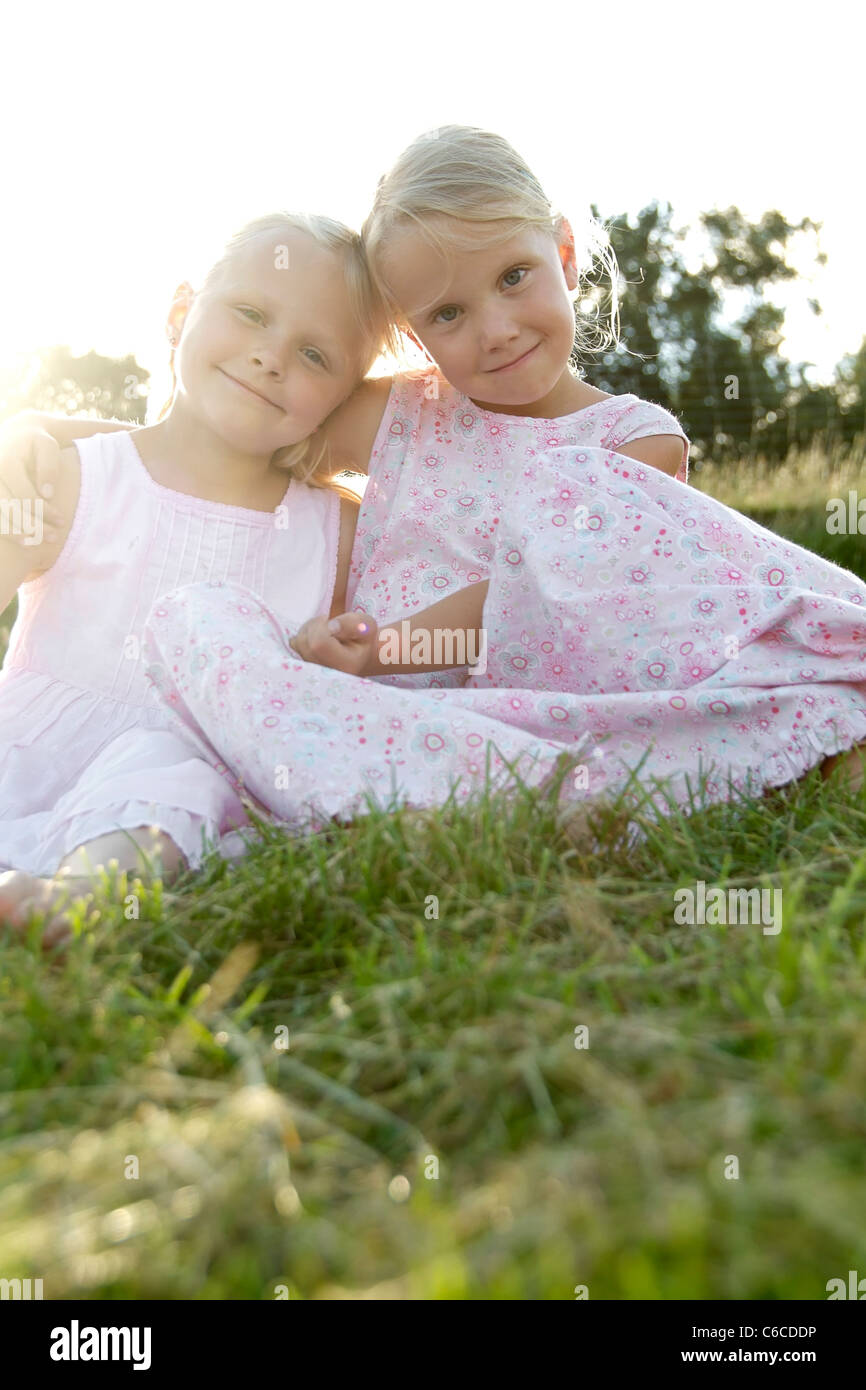 Portrait of two girl friends putting their arms around their shoulders in summer, Eyendorf, Lower Saxony, Germany, - Stock Image