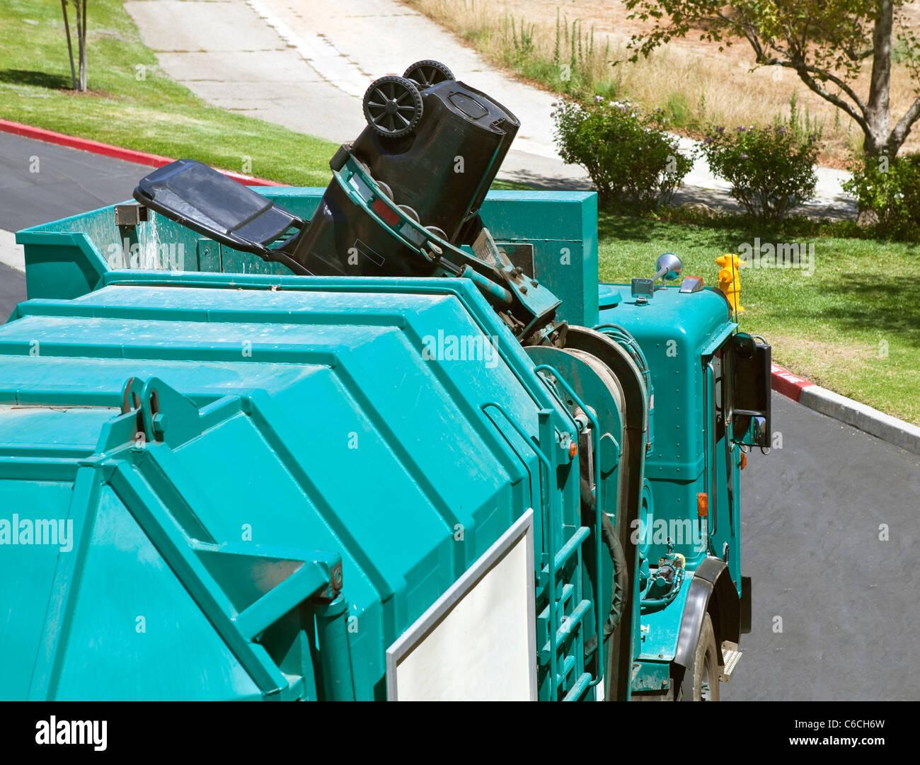 Municipal robotic arm trash truck dumps a large black can. - Stock Image