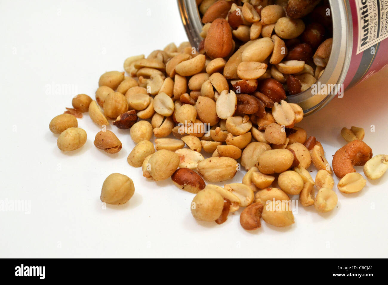 A open can of mixed nuts lays on it's side. - Stock Image