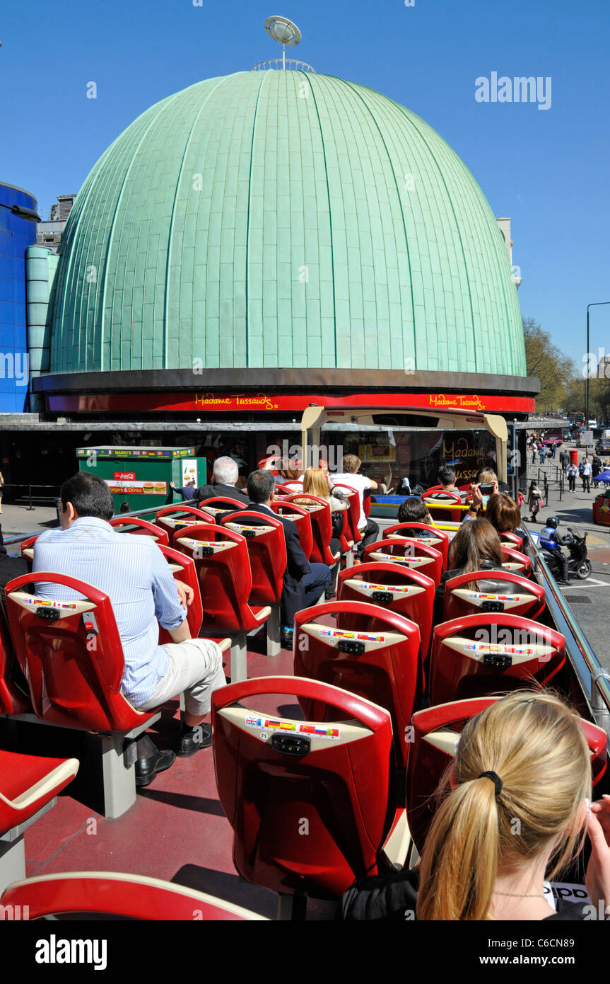Tourists open top sightseeing tour bus & Madame Tussauds green copper dome roof of one time London Planetarium - Stock Image