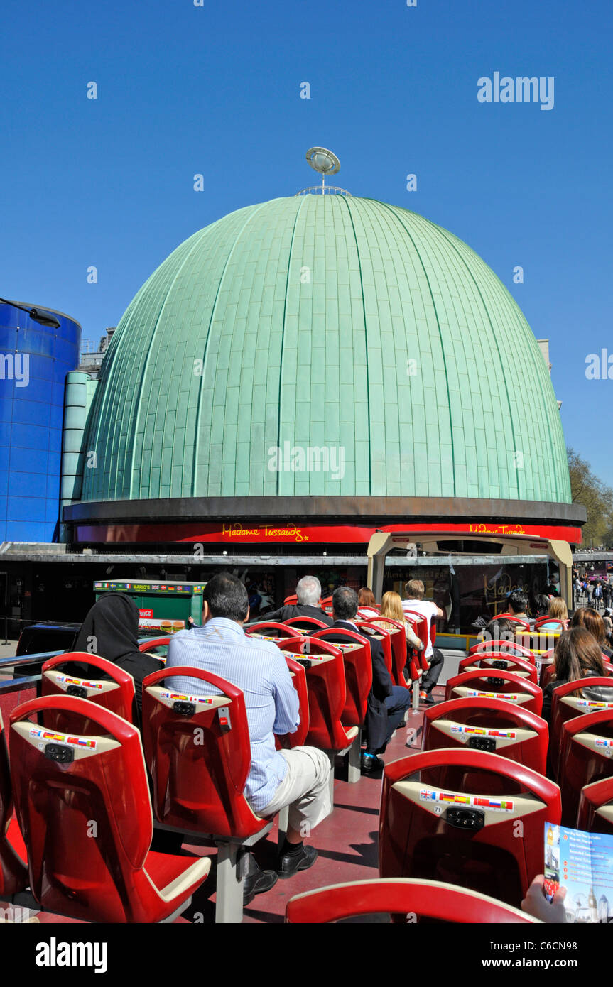 Tourists on open top double decker sightseeing tour bus outside Madame Tussauds green copper roof London England - Stock Image