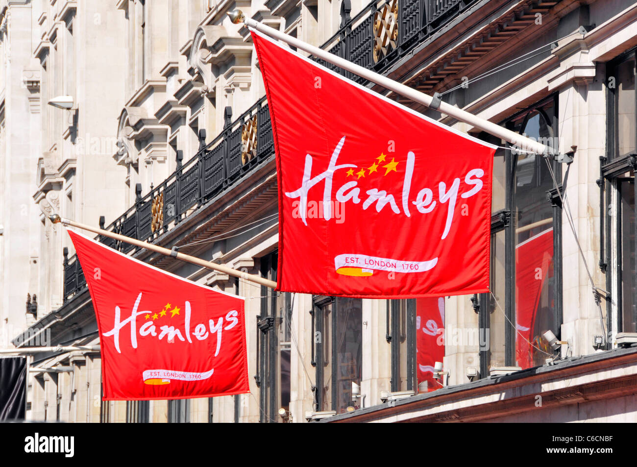 Street scene Hamleys logo on banners at famous flagship retail toy shop store business in London West End shopping - Stock Image