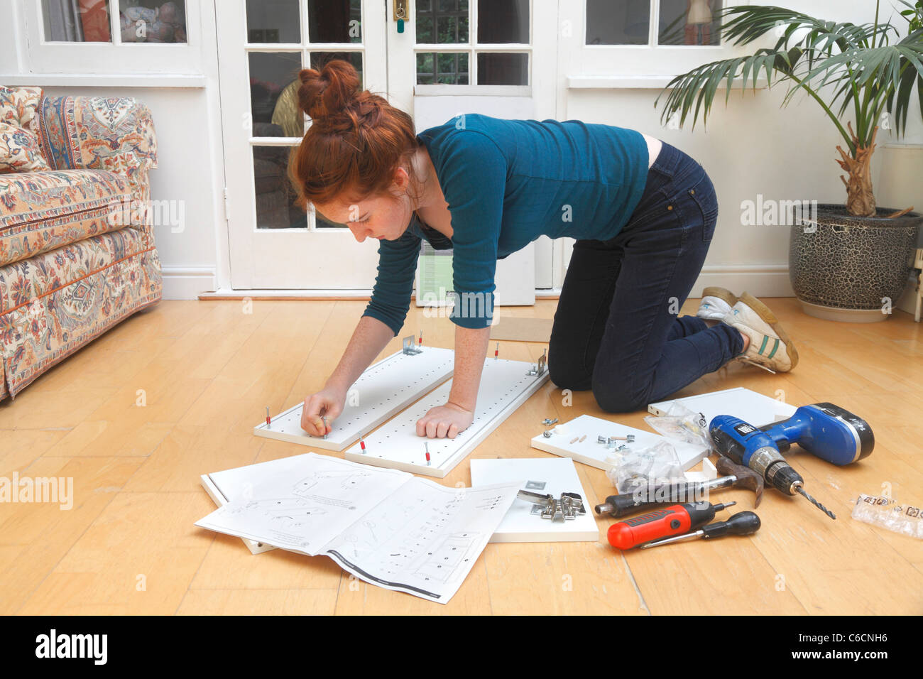 Young girl making a cabinet from a 'flat Pack' DIY kit. - Stock Image