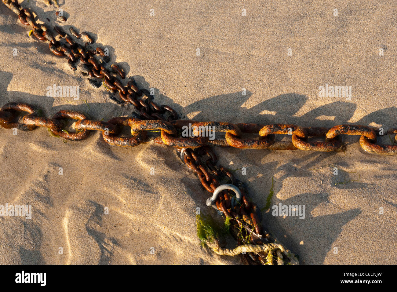 Rusting Chains sit on sand at the harbour of St Ives Cornwall. - Stock Image