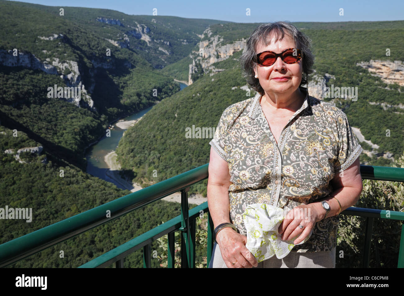 Elderly lady poses for photograph at viewpoint above Gorges d'Ardeche Gard France - Stock Image