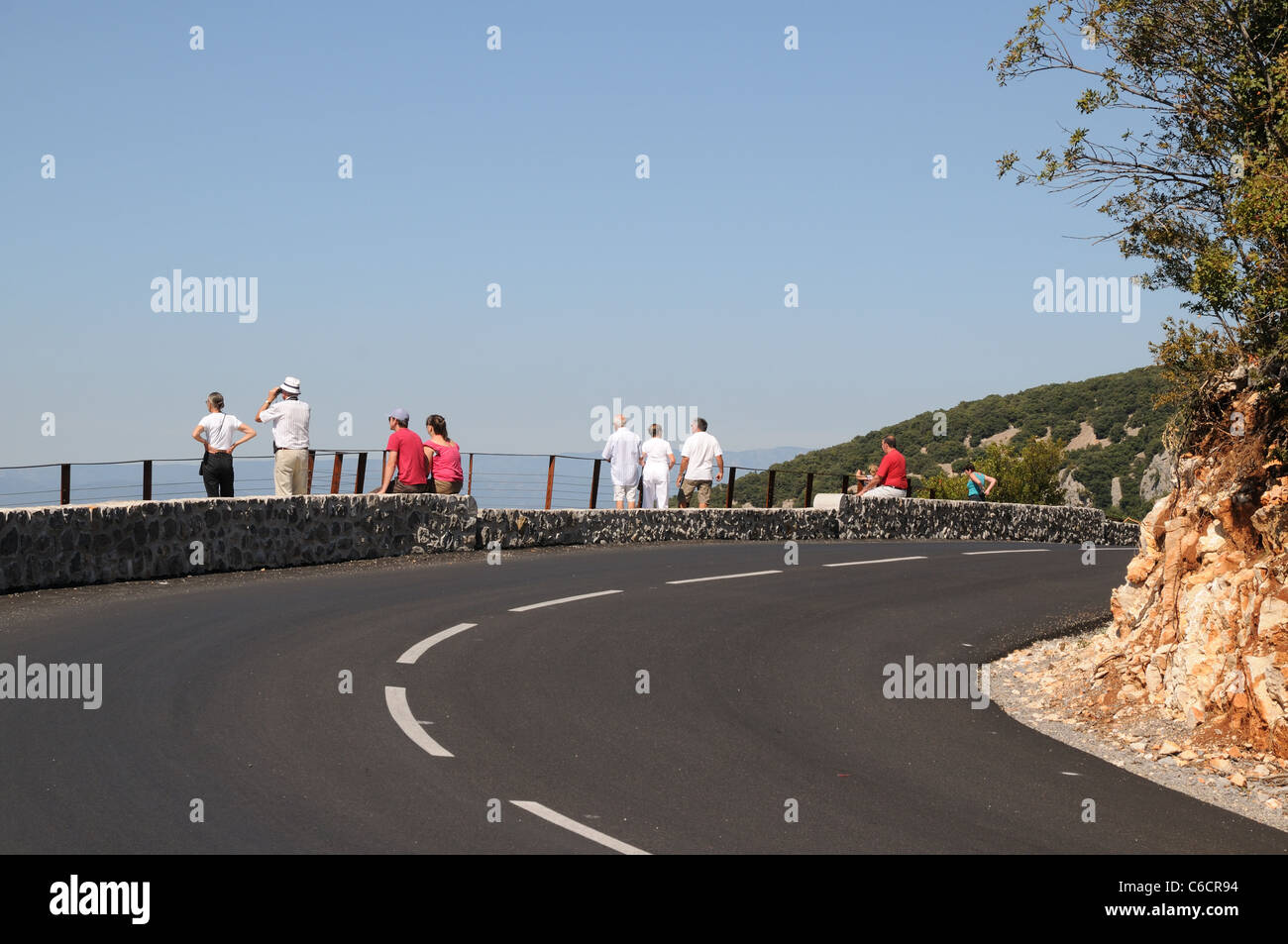 Road and viewpoint above Gorges d'Ardeche Gard France with tourists silhouetted against blue sky enjoying dramatic - Stock Image