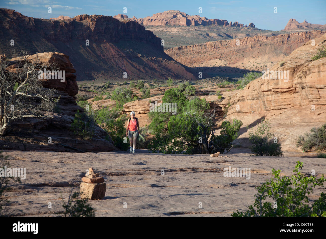Hiker on Trail to Delicate Arch in Arches National Park - Stock Image