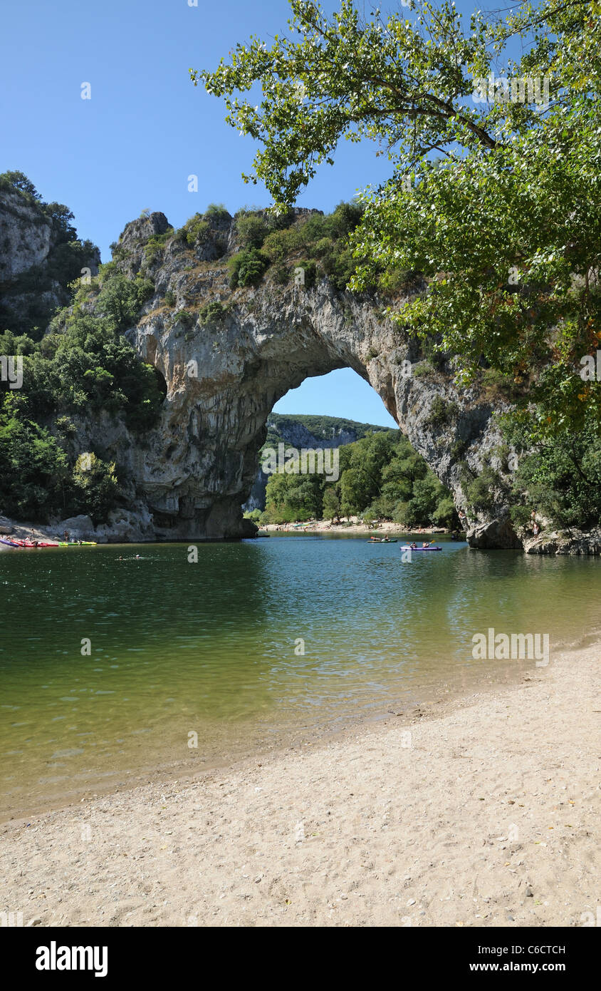 Pont d'Arc rock archway over the Ardeche river Gorges d'Ardeche Gard France with canoes and tourists sunbathing Stock Photo