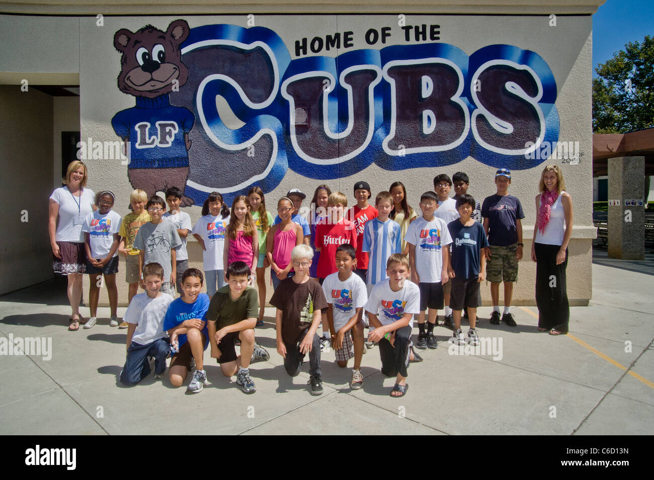 A happy group of students in a college-sponsored summer learning project pose for a group photo before a mural at - Stock Image