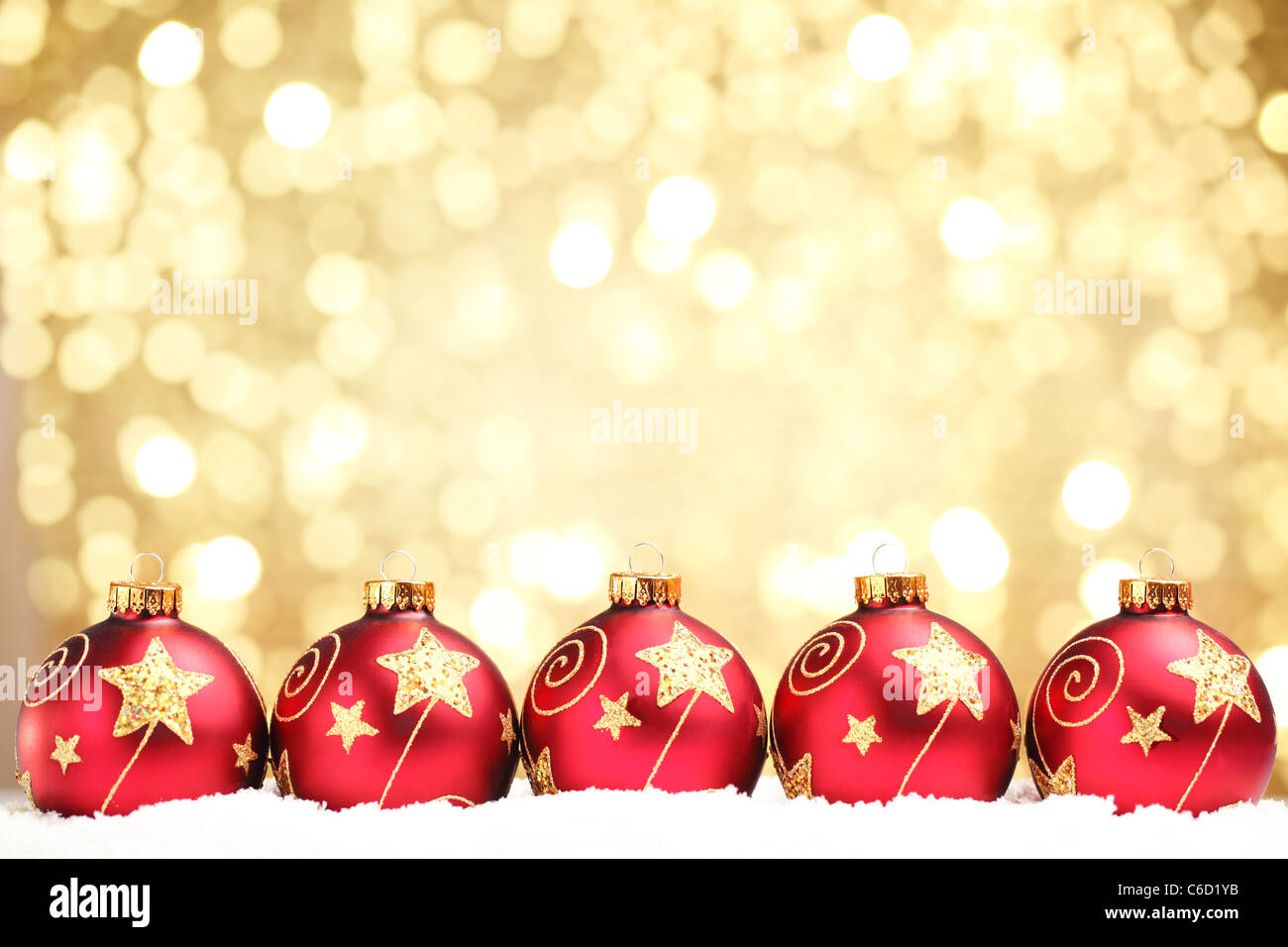 Row of shiny red christmas balls on abstract light background. - Stock Image