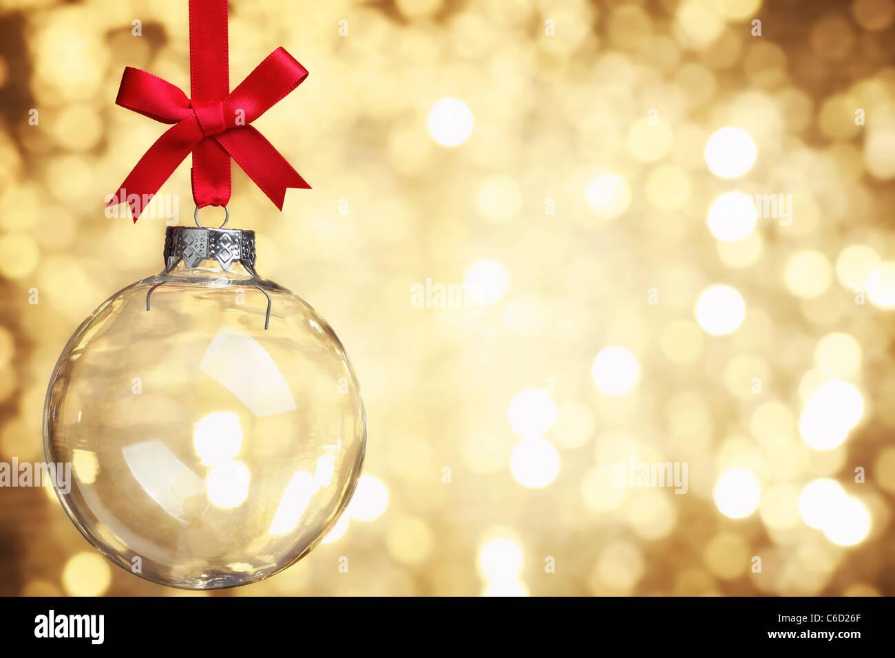Closeup of glass Christmas ball on abstract light background. - Stock Image