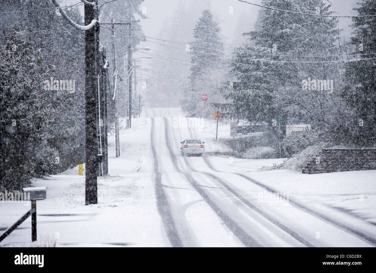 Car driving on residential street during snowstorm, Seattle, Washington, USA - Stock Image