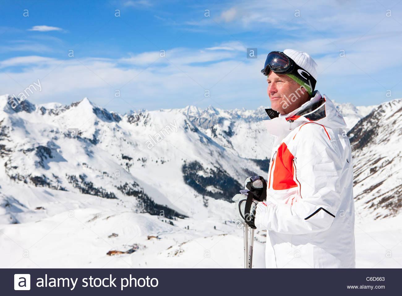 Smiling man with ski poles on snowy mountain - Stock Image