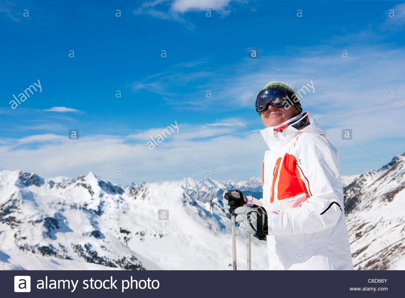 Smiling man wearing ski goggles and holding ski poles on snowy mountain - Stock Image