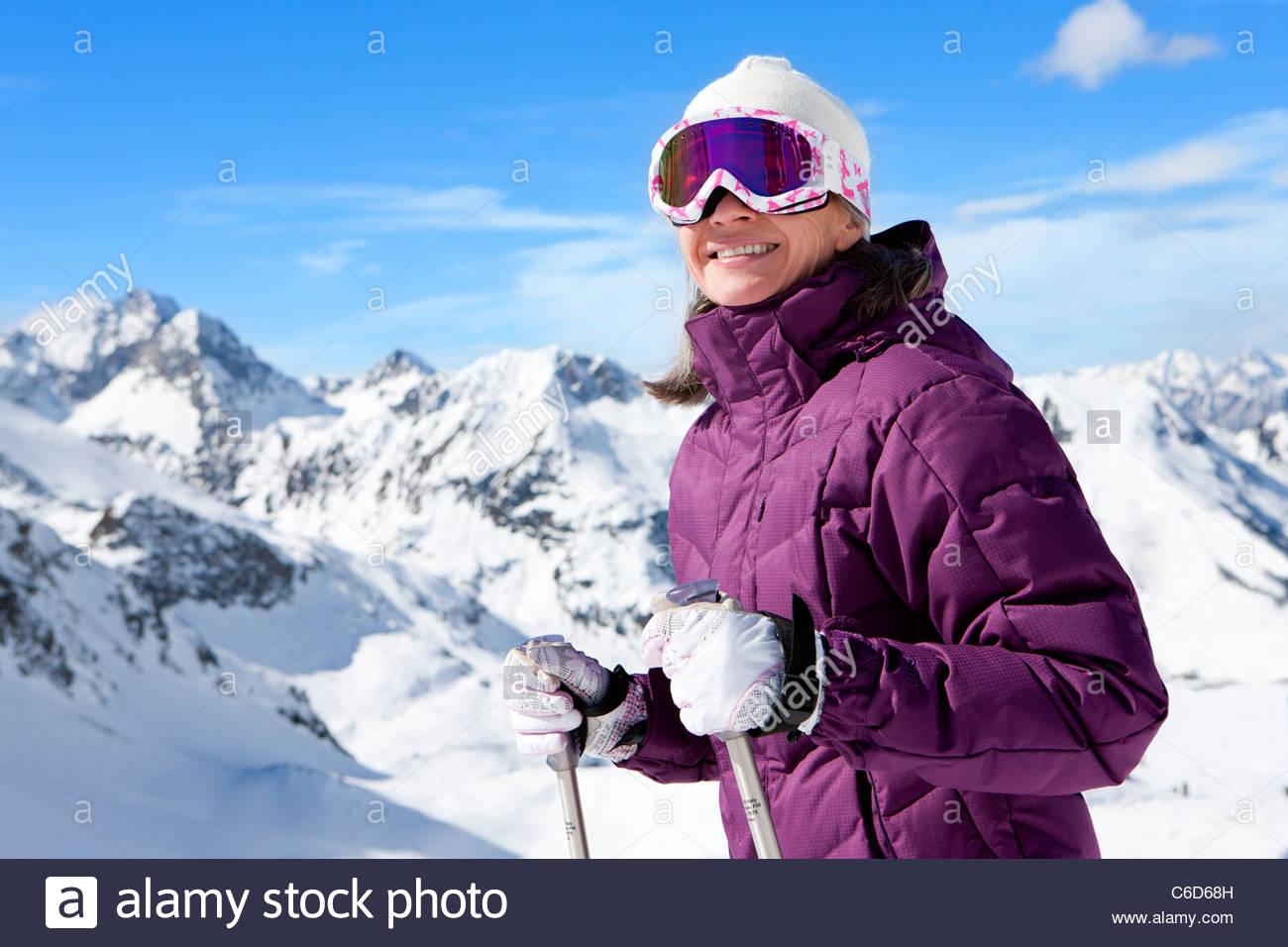 Smiling woman wearing ski goggles and holding ski poles on snowy mountain - Stock Image