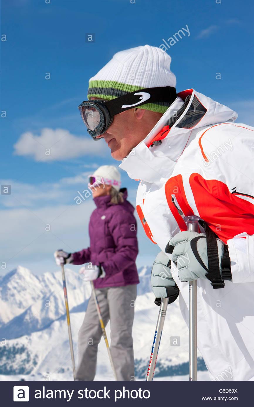 Couple wearing ski goggles and holding ski poles on snowy mountain - Stock Image