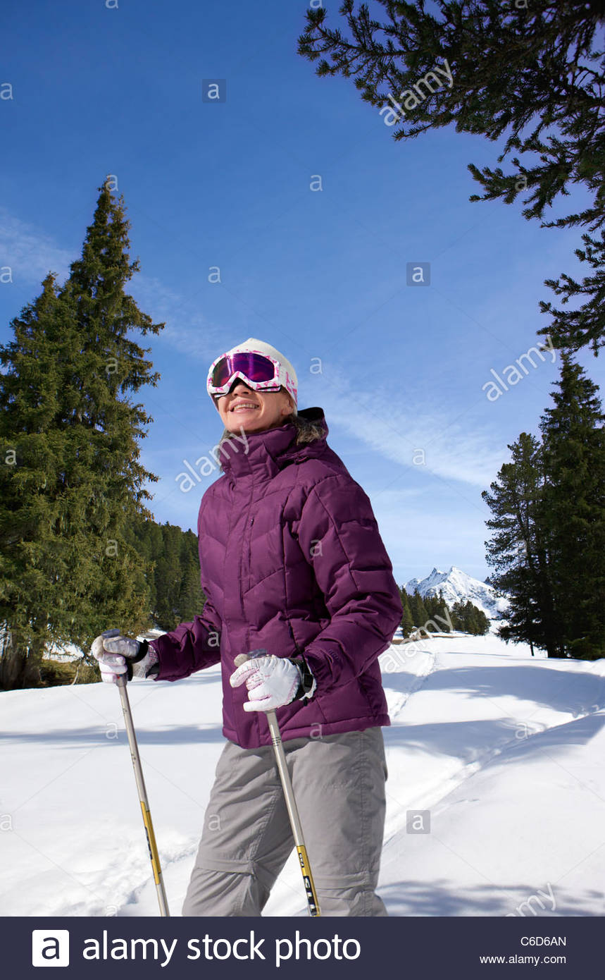Smiling woman wearing ski goggles and holding ski poles in snow - Stock Image