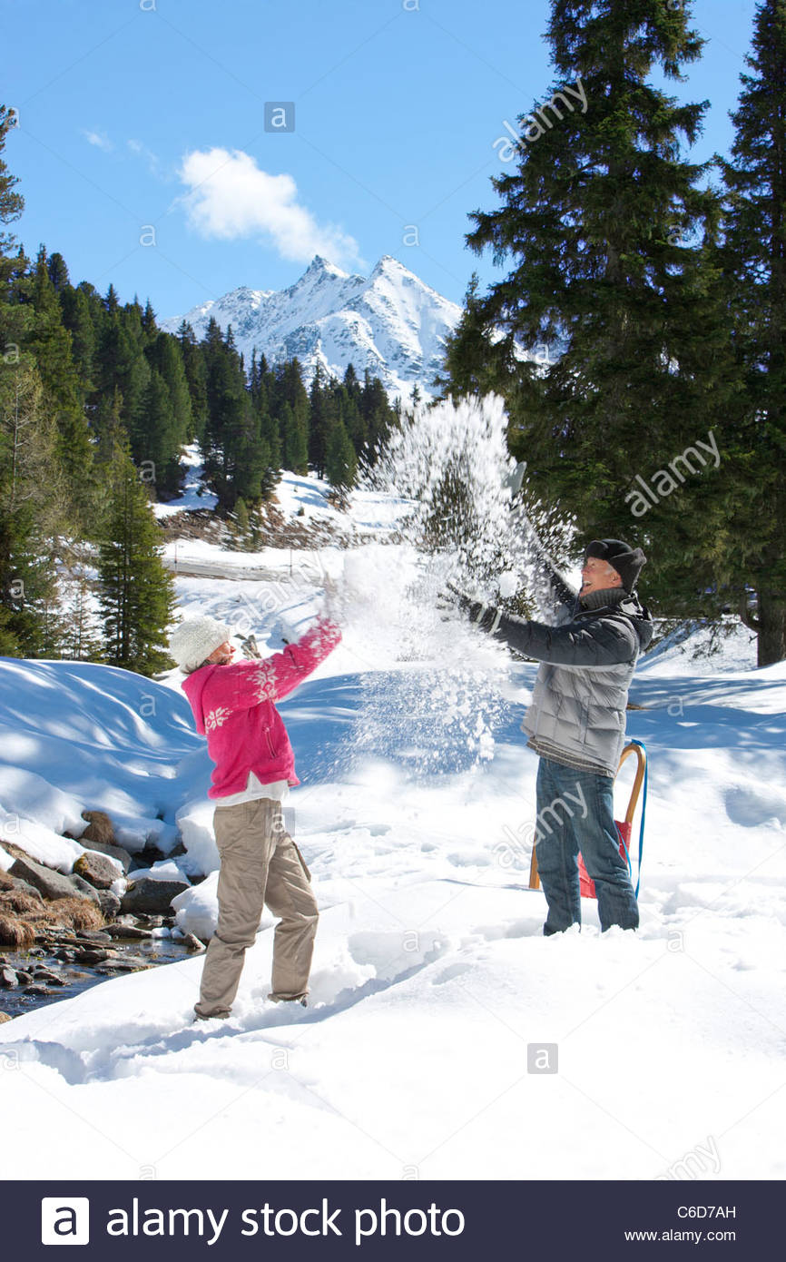 Playful couple throwing snow in woods below mountain - Stock Image