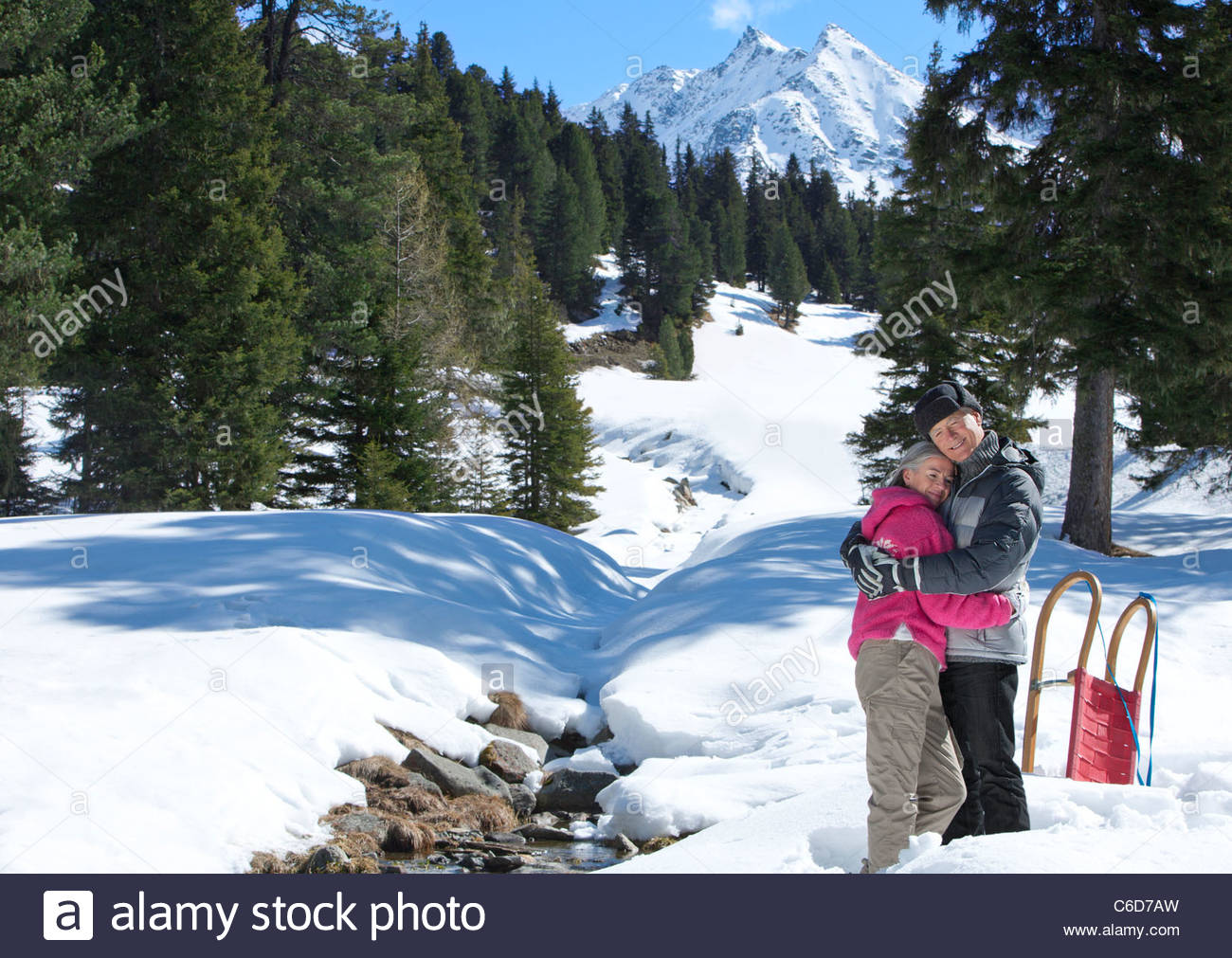 Smiling couple hugging in snowy woods below mountain - Stock Image