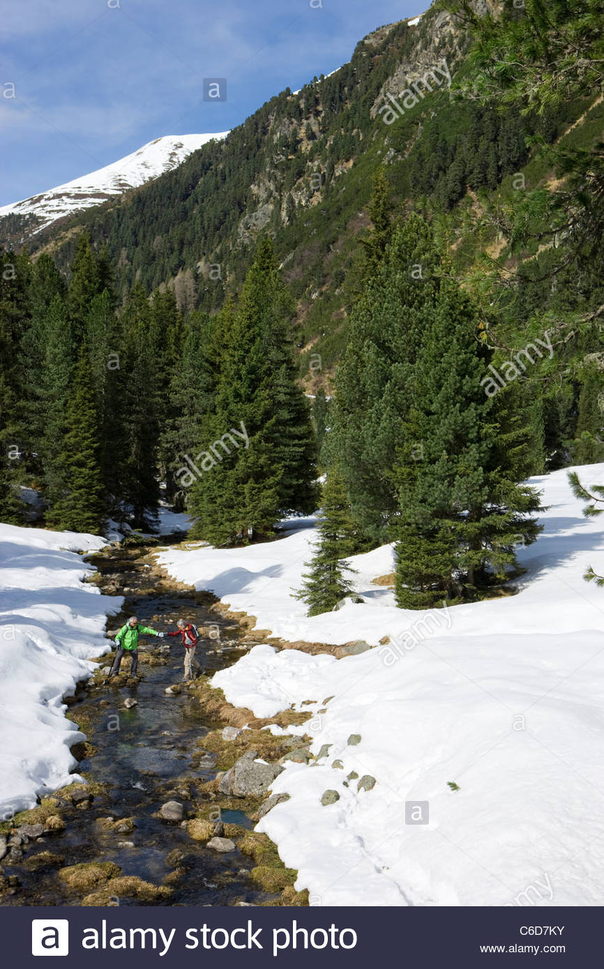 Distant view of couple crossing stream in snowy woods - Stock Image