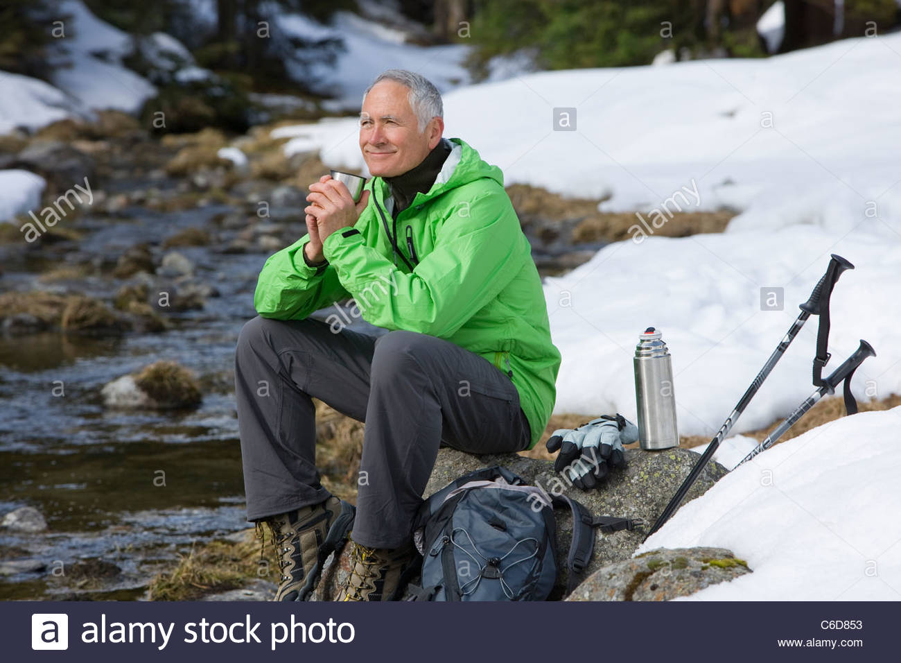 Smiling man with backpack and ski poles sitting at edge of stream in snowy woods - Stock Image