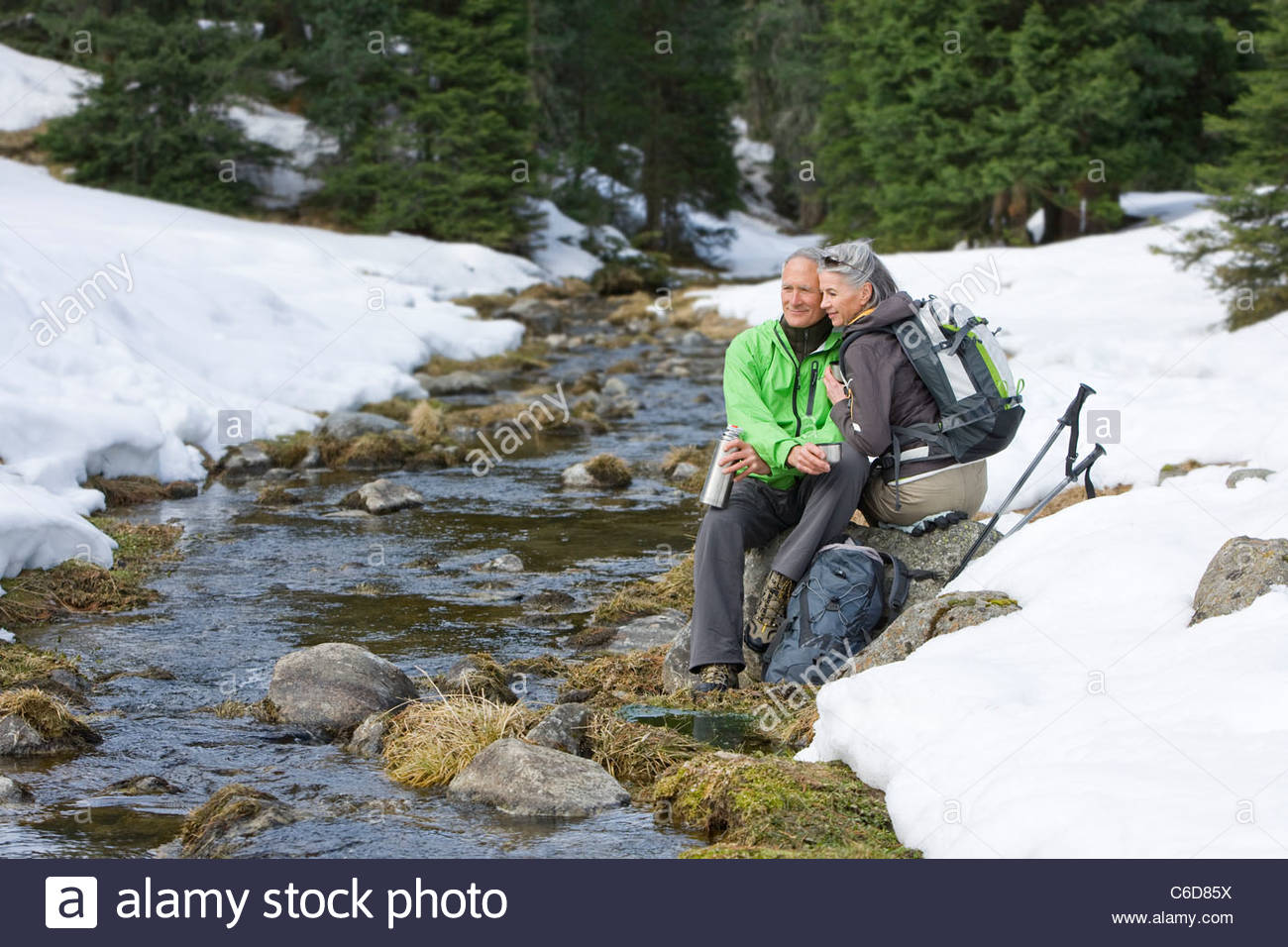 Couple with backpacks hugging at edge of stream in snowy woods - Stock Image