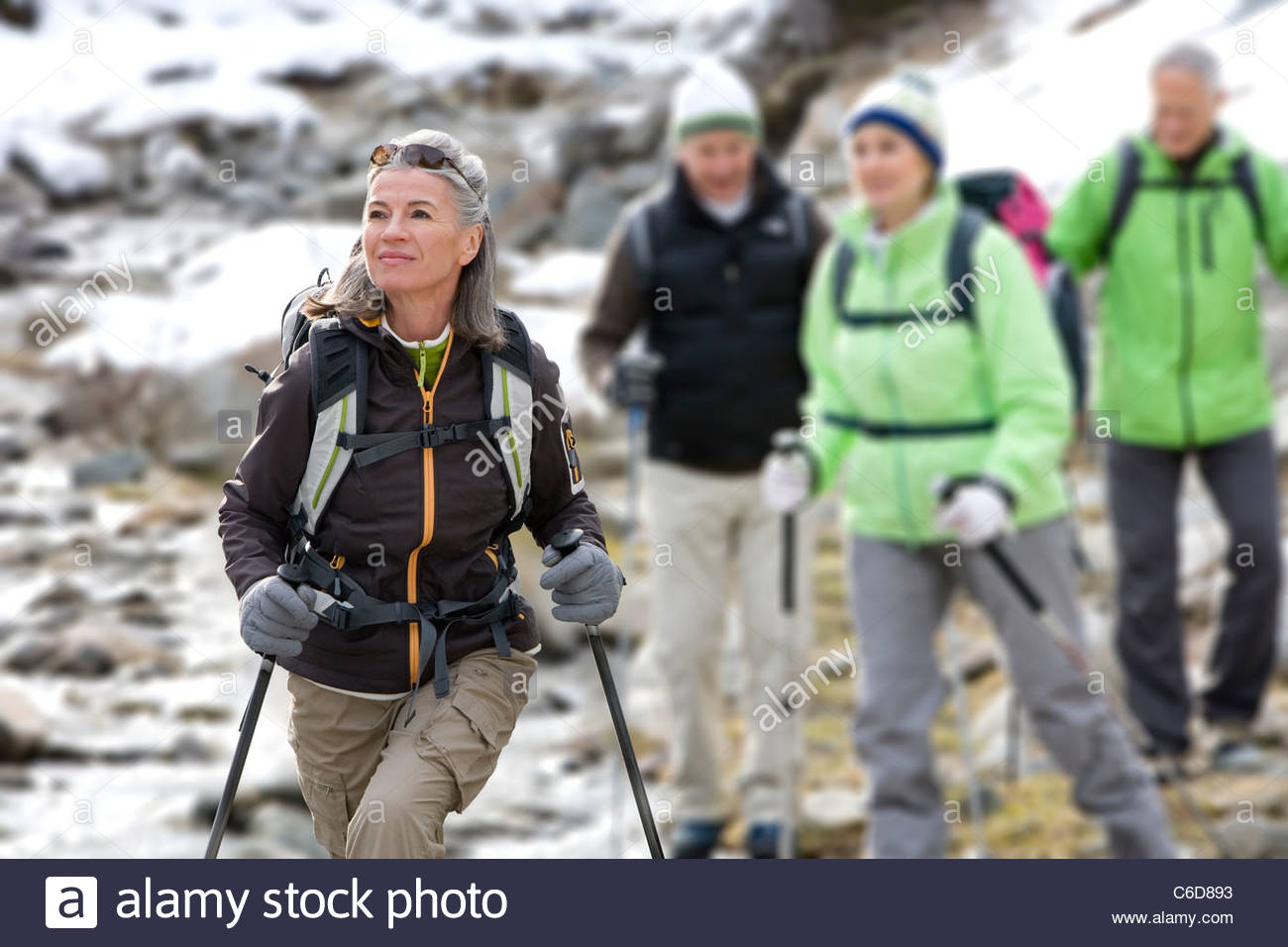 Senior couples with ski poles crossing stream - Stock Image