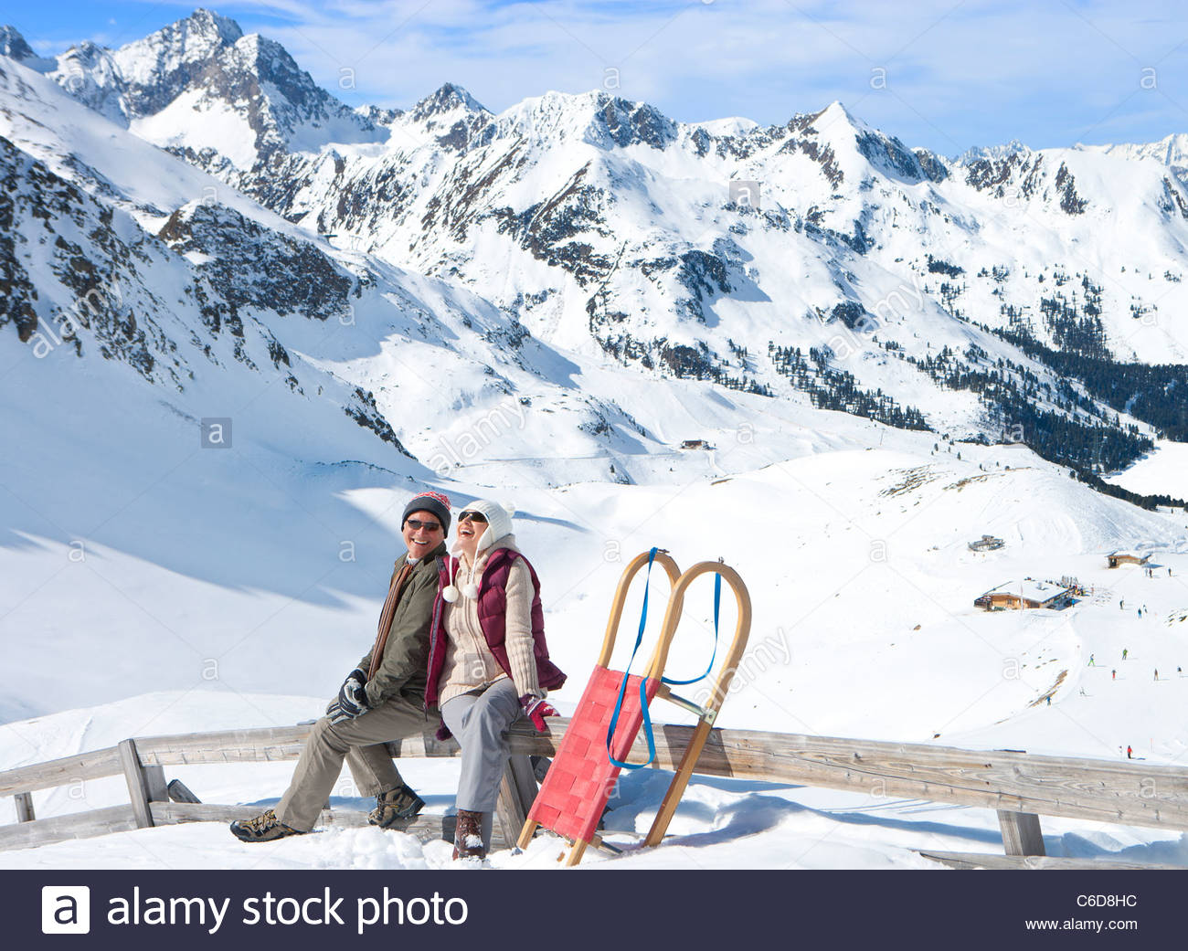 Smiling senior couple with sled siting on fence on snowy mountain - Stock Image