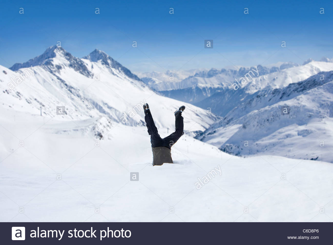 Man upside-down in snow on mountain Stock Photo
