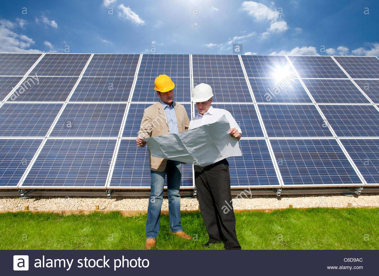 Technicians holding blueprints talking near large solar panels - Stock Image